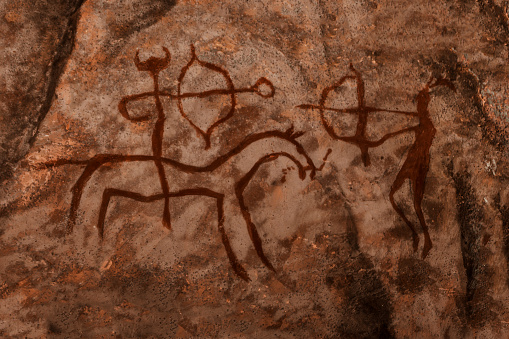 istock iDrawing of ancient hunters on the wall of the cave. 1144596538