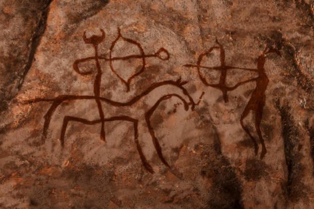 mağaranın duvarında eski avcılar yayılan. - mağara resmi stok fotoğraflar ve resimler