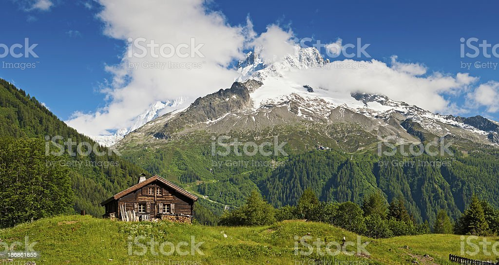 Idyllic Alpine chalet summer mountain meadow panorama Alps stock photo