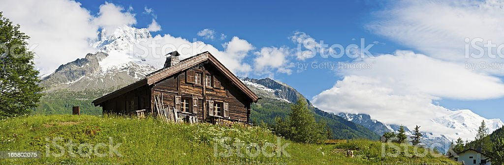 Idyllic Alpine chalet summer wildflower meadow panorama stock photo
