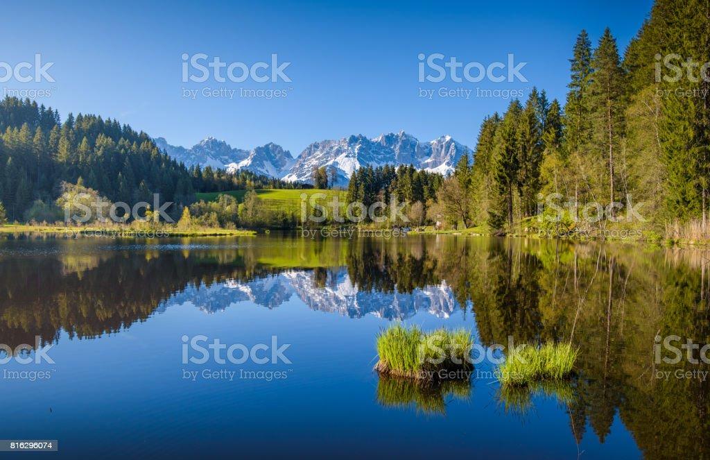 Idyllic alpine scenery, snowy mountains mirroring in a small lake, Kitzbühel, Tyrol, Austria stock photo