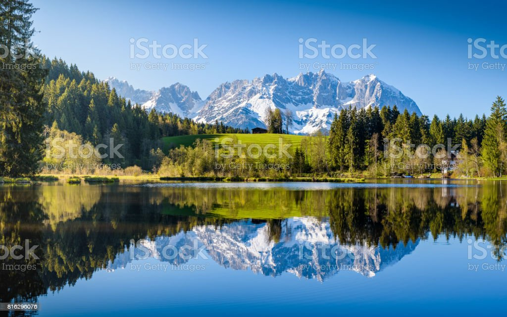 Idyllic alpine scenery, snowy mountains mirroring in a small lake, Kitzbühel, Tyrol, Austria stock photo
