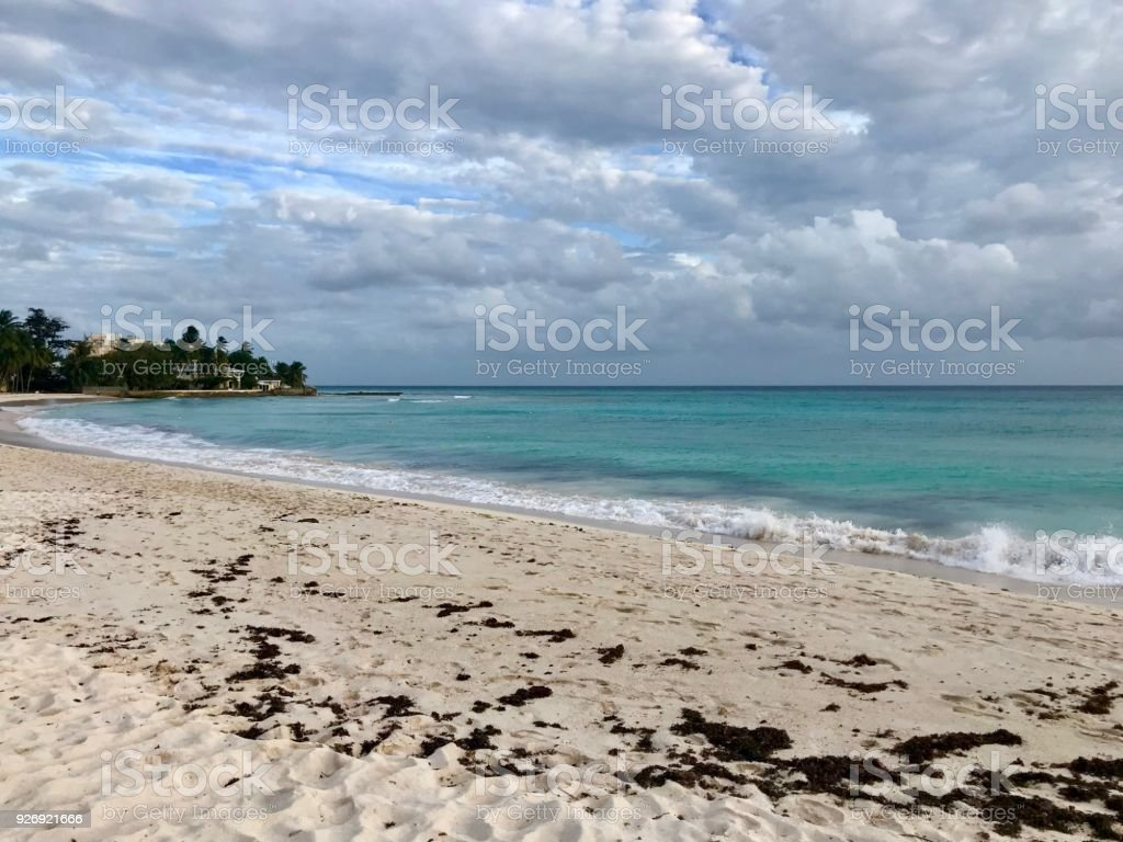 Idyllic and beautiful beach in Barbados: Nobody, white sand, turquoise water, waves and white clouds stock photo