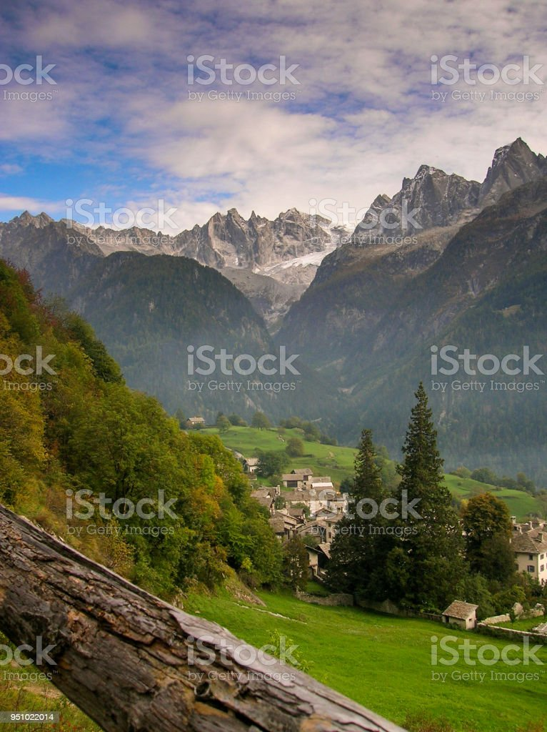 idyllic and picturesque mountain village in the Alps of Switzerland with a great mountain landscape view behind stock photo