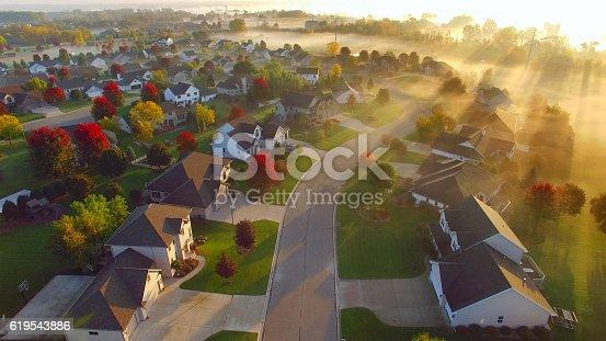 Idyllic wealthy Autumn neighborhood shrouded in fog at dawn, Fall colors.