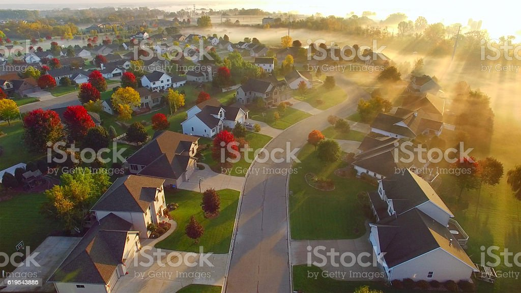 Idyllic Autumn neighborhood shrouded in fog at dawn. - Photo