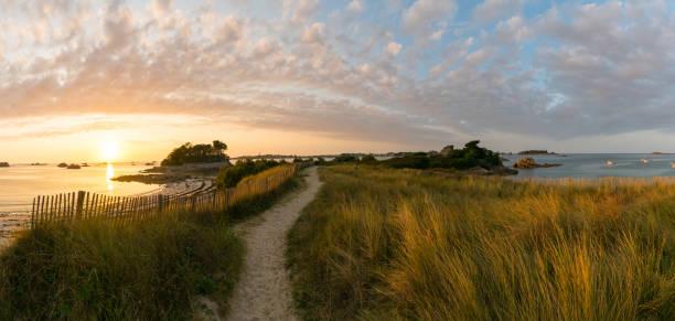 idyllisches Küstenpanorama bei Sonnenuntergang mit sandigem Fußweg, der in die Ferne führt – Foto