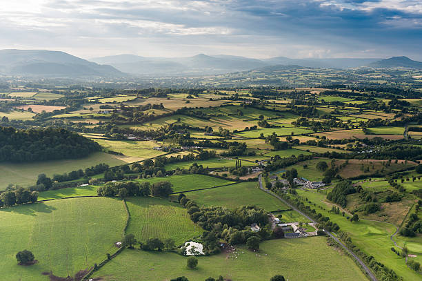 Idyllic country meadows misty mountains aerial landscape Rays of sunlight illuminating the picturesque patchwork quilt landscape of green fields, farms and misty mountains under panoramic skies from high in a hot air balloon. ProPhoto RGB profile for maximum color fidelity and gamut. brecon beacons stock pictures, royalty-free photos & images
