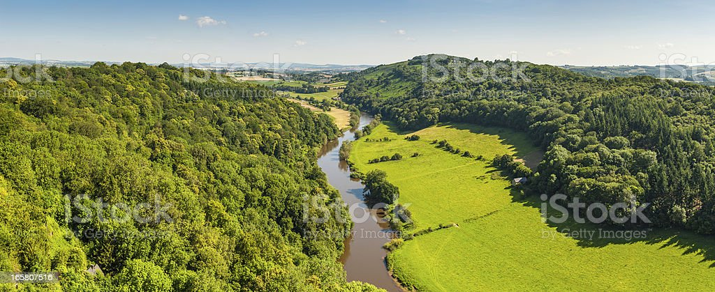 Idyllic country river meadering through green summer valley stock photo