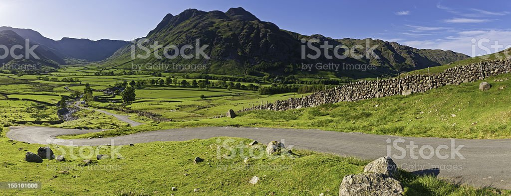 Idyllic country road over vibrant green landscape Lake District stock photo
