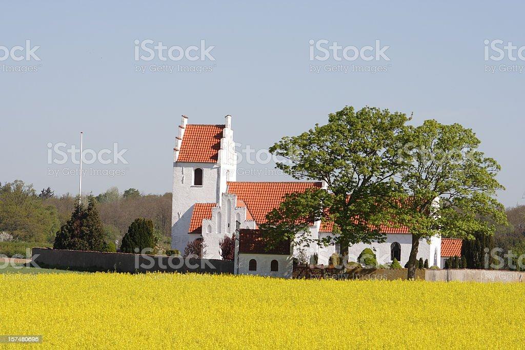 Idyllic country side parish church behind oilseed rape field stock photo