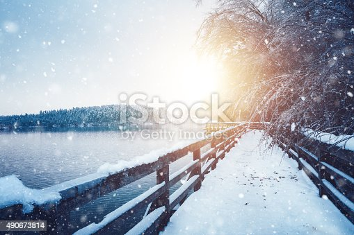 Frozen footpath with a wood fence by the lake on a snowy winter morning.