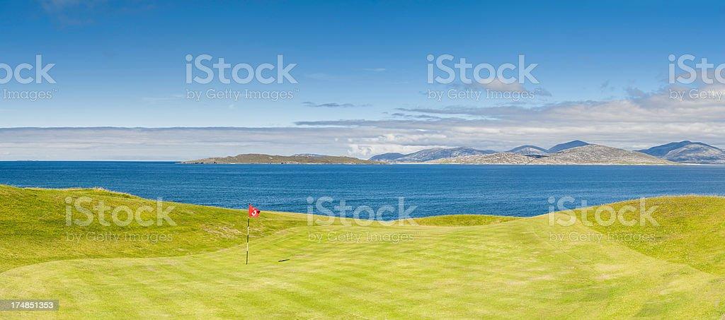 Idyllic golf course green flag overlooking ocean panorama Scotland stock photo