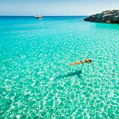Idyllic holidays: girl floating in fresh clean turquoise water.