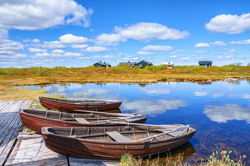 Idyllic landscape view with row boats at a mountain huts jetty