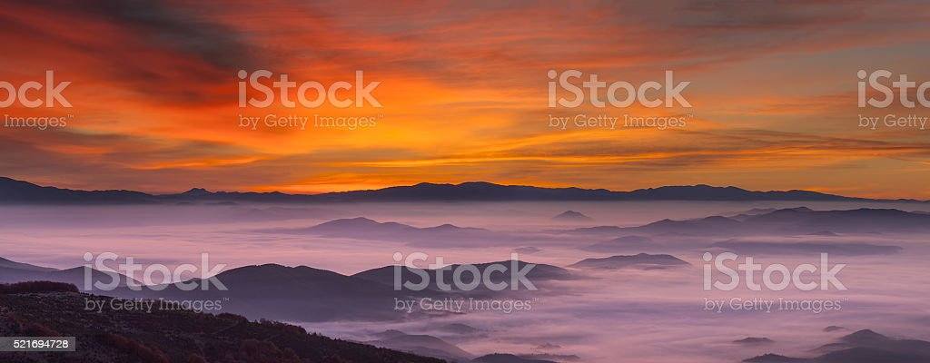 Idyllic mountain landscape at foggy dawn stock photo