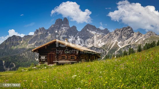 istock Idyllic mountain landscape in the alps: Mountain chalet, meadows and blue sky 1329178002