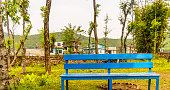 Idyllic mountain village bench and landscape, kathmandu nepal. IThe garden is surrounded with trees and greenery. Very quiet place for tourist. Bench is blue coloured.