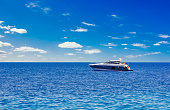 idyllic picturesque expensive cruise vacation concept photography of Mediterranean sea scenery landscape and lonely yacht floating on water, blue sky with white clouds background, empty space for text