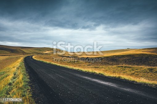 Black dirt road leading through Icelandic landscape.
