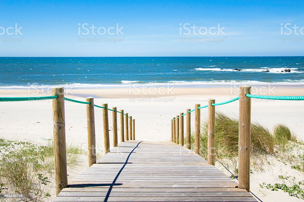 Idyllic sand beach with blue sea, blue sky and gentle waves stock photo