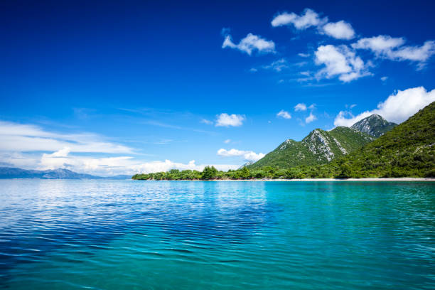 Idyllic seascape - Island, crystal clear Adriatic Sea and Blue Sky with White Clouds stock photo