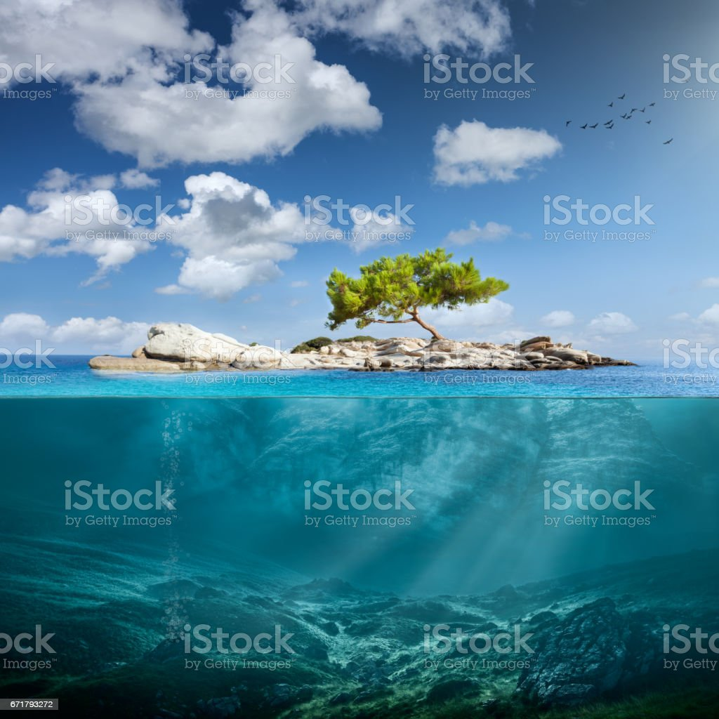 Idyllic small island with lone tree in the ocean stock photo