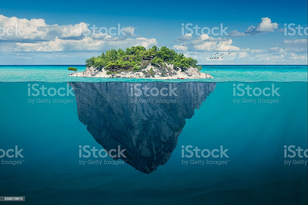 Idyllic solitude island with green trees in the ocean stock photo