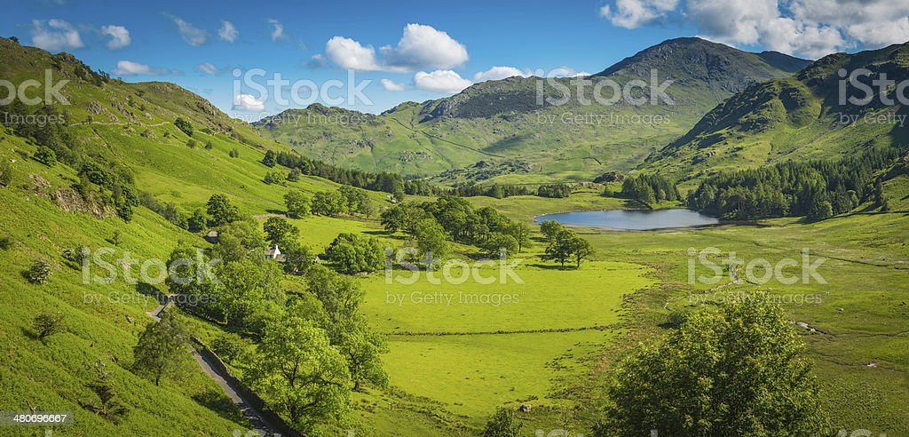 Idyllic summer mountain valley green landscape blue skies panorama Cumbria stock photo