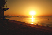 Wide shot of Egyptian beach during a vibrant sunrise hour in from of the empty and calm sea.