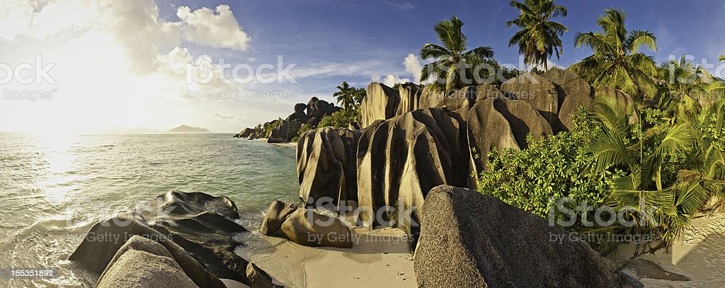 Idyllic tropical island beach sunset palm trees panorama royalty-free stock photo