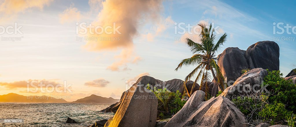 Idyllic tropical island sunset over palm tree beach ocean lagoon stock photo