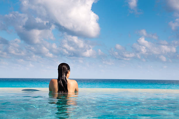 """Idyllic Vacation in Caribbean Resort Hotel Pool Hz """"Subject: A young woman vacationer relaxing in an infinity pool of a tropical beach resort hotel.Location: Caribbean Sea, Cancun, Riviera Maya, Mexico."""" infinity pool stock pictures, royalty-free photos & images"""