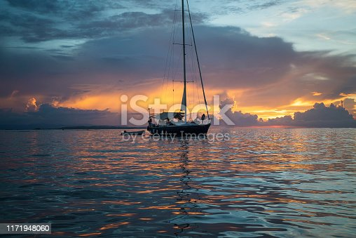 Cloudscape reflecting in ocean. Sailboat silhouette