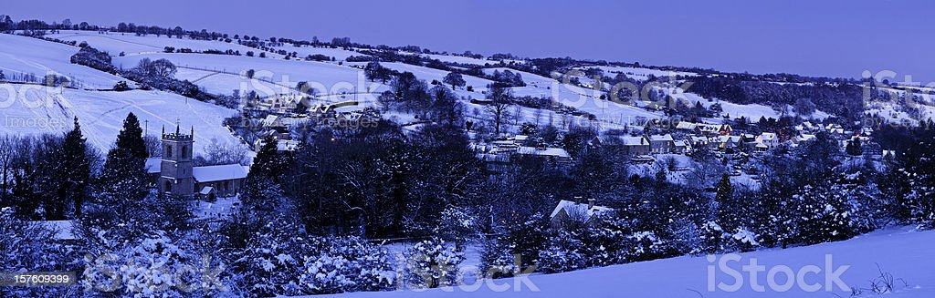 Idyllic winter village church cottages snow covered landscape Cotswolds UK stock photo