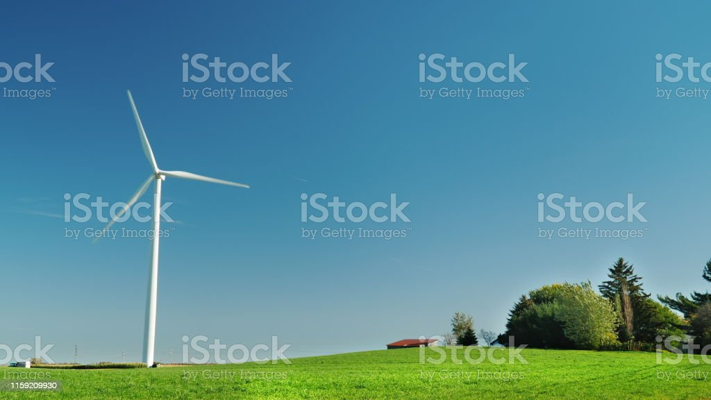 A wind turbine stands on a hill near the farm. Ideal picture of clean...
