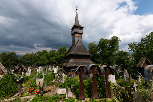 Ieud, Maramures, Romania - July 9, 2018: Ieud Hill Church and its graveyard, the oldest wood church in Maramures, Romania under a dramatic sky. The Church belongs to a collection of Wooden Churches of Maramures, UNESCO World Heritage Site.
