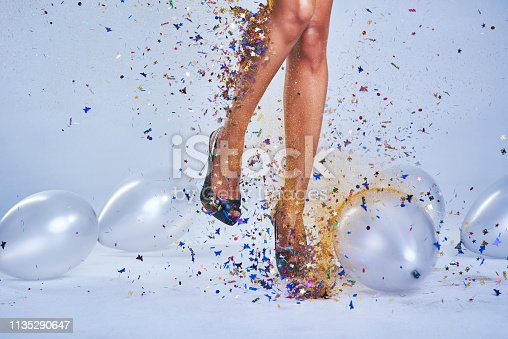 Studio shot of a young woman's legs in a pair of heels with confetti and balloons falling around
