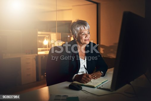 Shot of a mature businesswoman writing in a notebook and using a computer during a late night at work