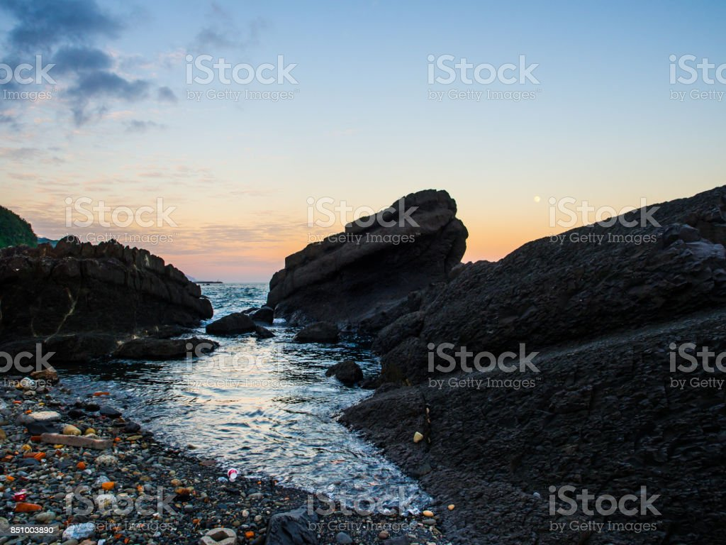 If no one would help to clean the messy stuff around the beach from tourists and travelers, the beauty of nature would have gone soon. Anyway, the black texture of rock and moon is beauty in Waiao, Taiwan stock photo
