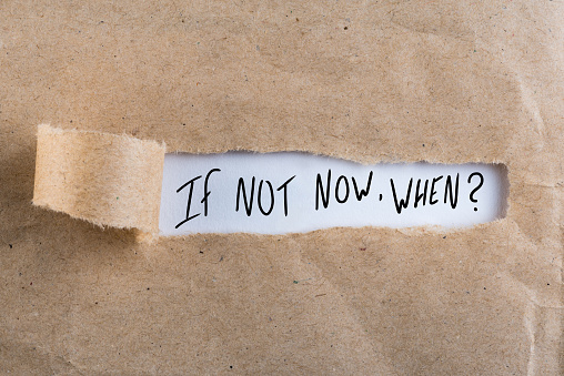 If Not Now When, appearing behind torn brown paper.
