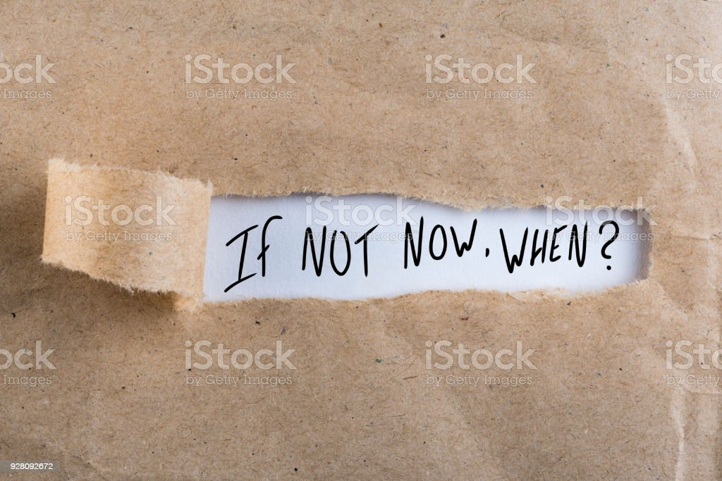 If Not Now When, appearing behind torn brown paper stock photo