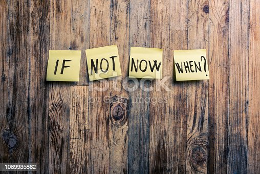 If not now when ? hand written on Post it notes on wood background