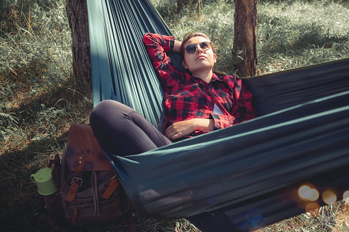 A young woman is sitting in a hammock she'd set close to the remote hut she owns. She's enjoying her day off work and noisy life.