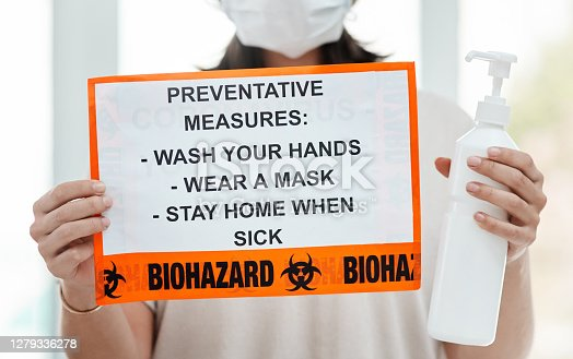 Shot of a woman holding up a sign with a list of COVID-19 prevention measures