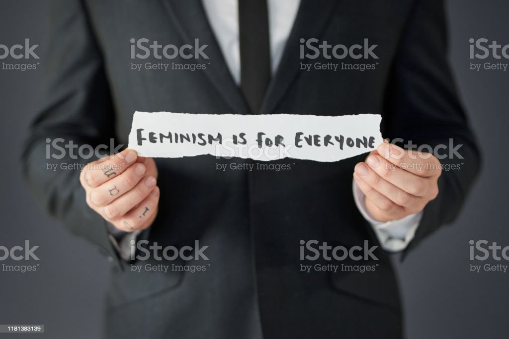 "If you believe in equality, you believe in feminism Studio shot of an unrecognizable businessman holding a piece of paper written ""#FEMINISM IS FOR EVERYONE"" against a grey background Adult Stock Photo"