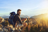 Shot of a young man using a smartphone while hiking up a mountain