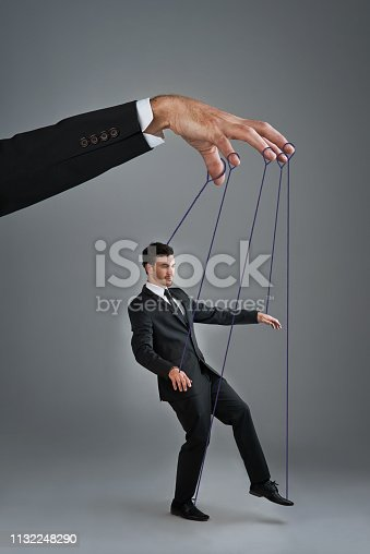Studio shot of a young businessman being controlled like a puppet by a giant hand against a gray background