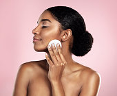 Studio shot of a beautiful young woman cleaning her face with cotton wool