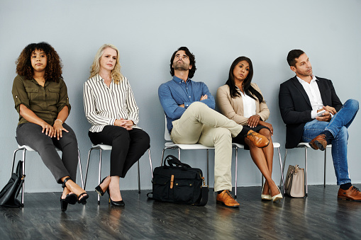 Studio shot of a group of businesspeople looking bored while waiting in line against a grey background